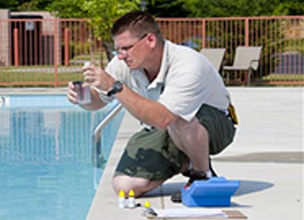 pool technician cleaning a family pool